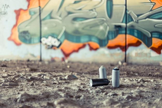 Latas de aerosol delante de graffiti en la pared