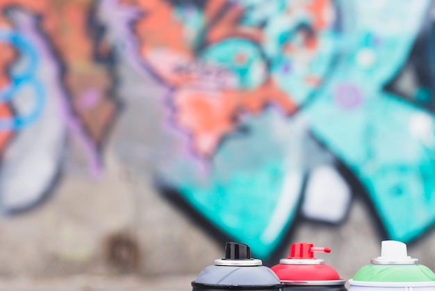 Latas de aerosol frente a la pared de graffiti