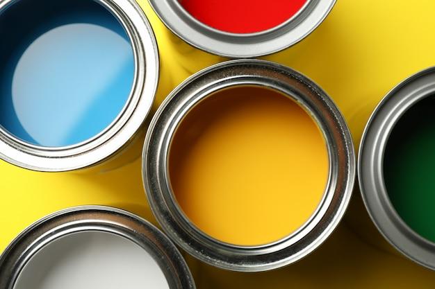 Latas de pintura sobre superficie amarilla y primer plano