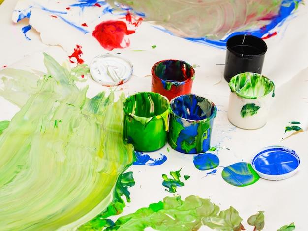 Latas de plástico multicolor con pinturas. fondo de trabajo del artista