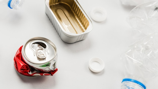 Latas y residuos plásticos sobre superficie blanca.