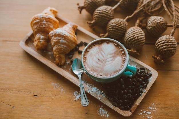 Latte art o capuchino en taza verde con pan y granos de café en la mesa