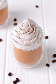 Latte de calabaza con crema batida y especias en mesa de madera blanca