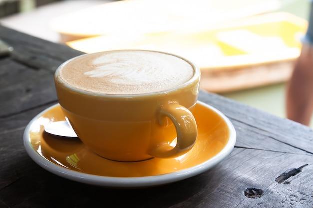 Latte caliente en taza amarilla en mesa de madera