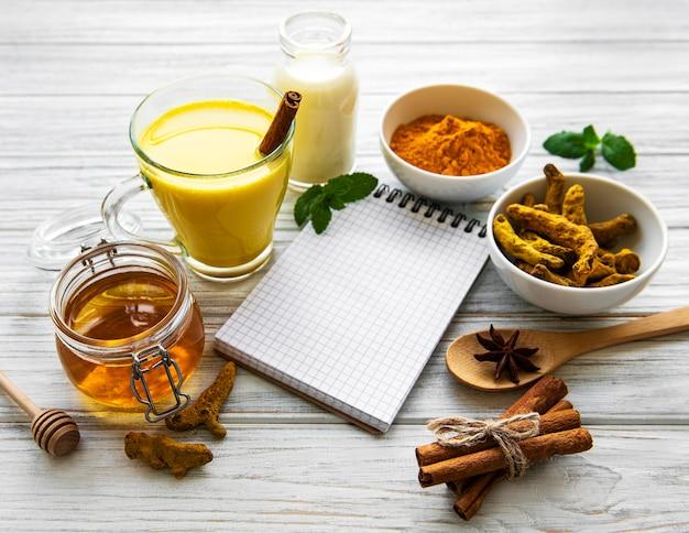 Latte de cúrcuma dorada en un vaso, especias y libro de recetas sobre fondo blanco de madera