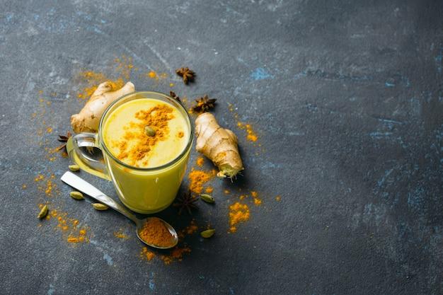 Latte dorado en la vista superior de la mesa negra. ingredientes para cocinar café con leche amarillo