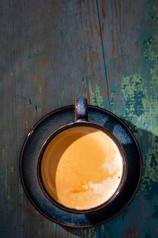 Latte con espuma, taza de café azul sobre fondo de madera