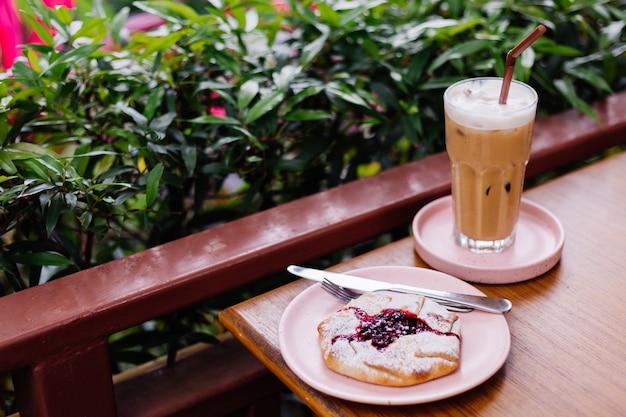 Latte helado en vidrio sobre un soporte de color rosa sobre la mesa de madera y tarta de arándanos en el café de verano arbustos verdes