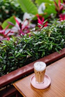 Latte helado en vidrio sobre un soporte rosa sobre una mesa de madera en el café de verano arbustos verdes
