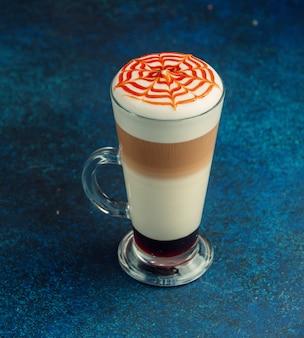 Latte macchiato con crema batida y tiras de caramelo en la parte superior