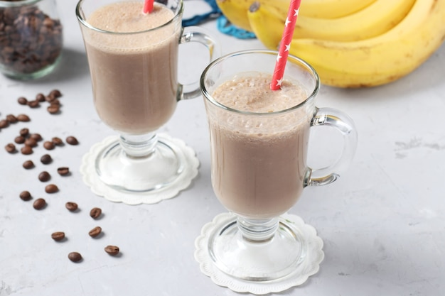 Latte de plátano con especias en dos vasos sobre fondo gris, primer plano. formato horizontal.