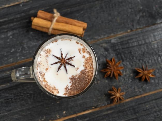 Latte de té casero con canela y anís sobre fondo negro rústico de madera en taza de vidrio