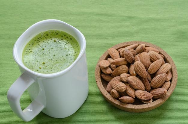 Latte de té verde caliente en tiempo perezoso con nueces almendras