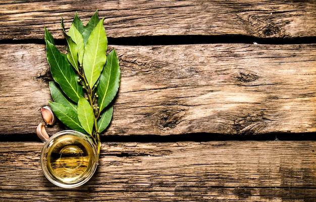 Laurel, ajo y aceite de oliva. sobre fondo de madera.