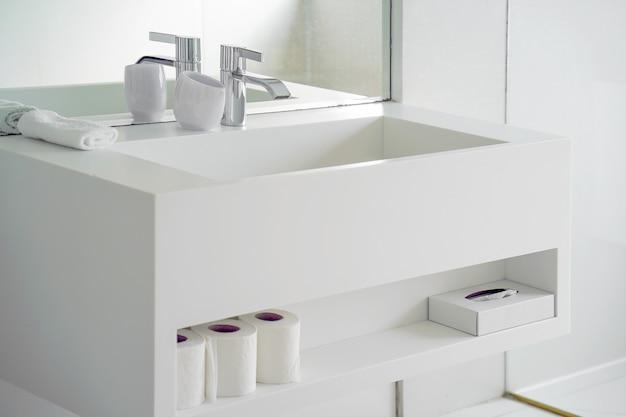 Lavabo blanco moderno con grifo. interior de baño con lavabo y grifería.