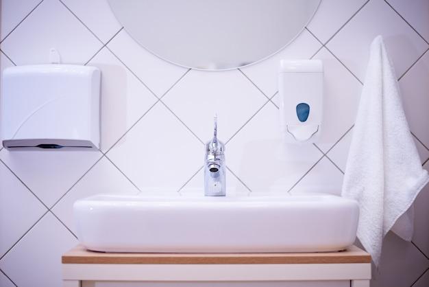 Lavabo blanco con una toalla y jabón en el salón de spa
