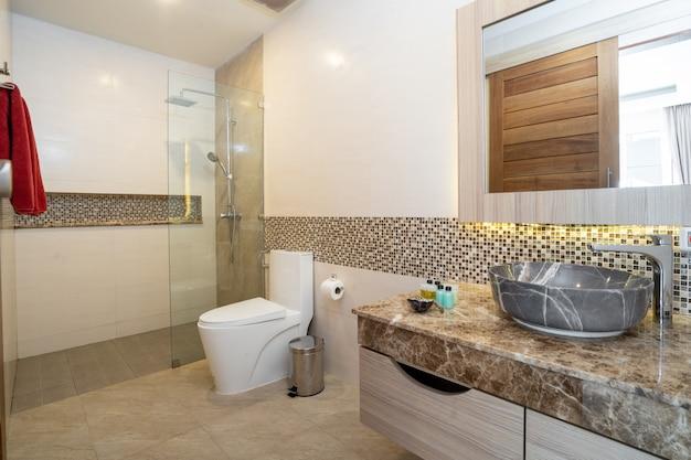 Lavabo con granito superior, inodoro y ducha en una casa