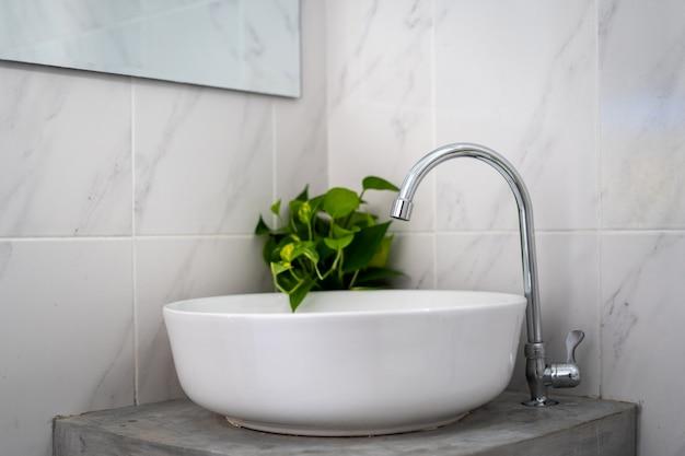 Lavabo redondeado blanco con grifo plateado y una planta en el baño