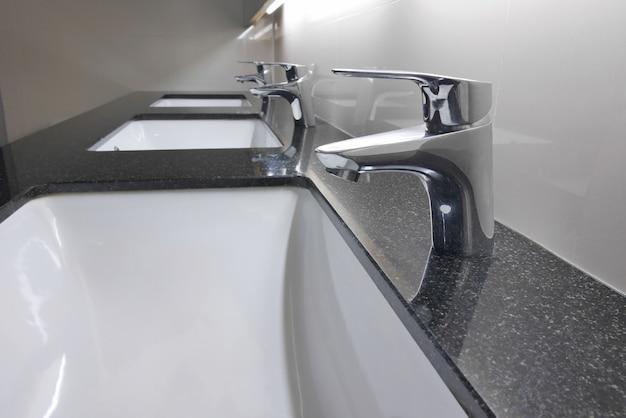 Lavabos y grifos blancos en el mostrador de granito en el baño