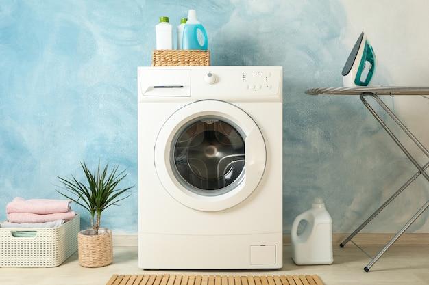 Lavadero con lavadora contra pared azul