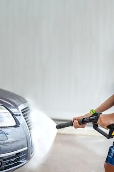Lavado de autos con agua a presión. autoservicio, publicidad de lavado de autos con espacio para copiar o pegar texto.