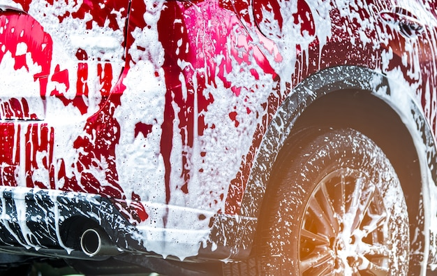 Lavado de autos suv compacto rojo con espuma antes del encerado del vidrio y revestimiento de vidrio del automóvil.