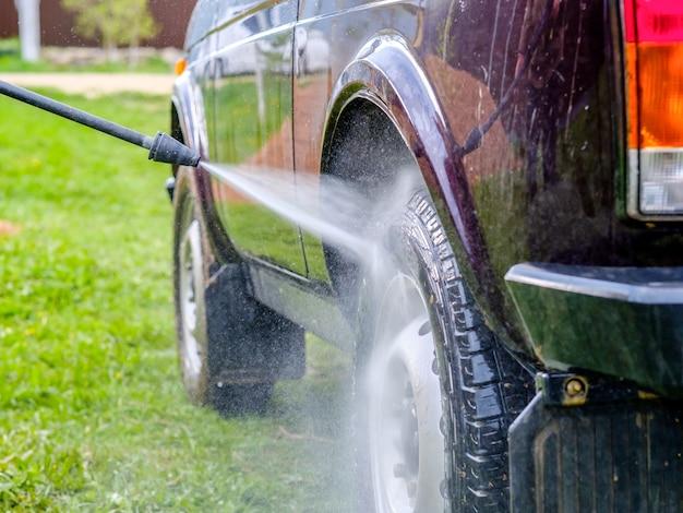 Lavado de coches por la tarde al aire libre con aparato de alta presión