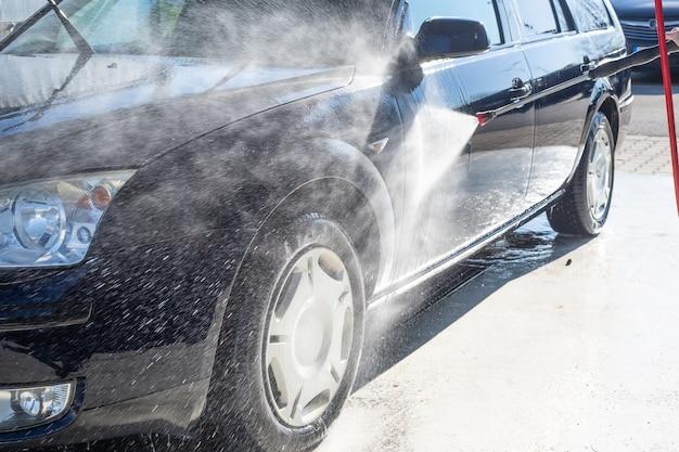 Lavado manual de automóviles, limpieza con agua a alta presión en el túnel de lavado, concepto de purificación