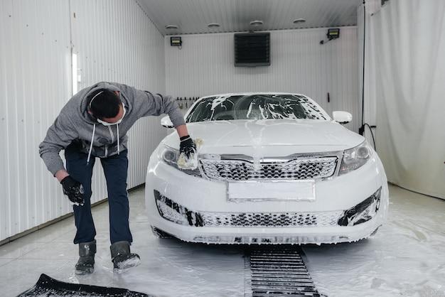 Lavado moderno con espuma y agua a alta presión de un automóvil blanco. lavado de autos.