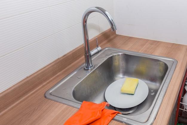 Lavado de platos con detergente y guantes.