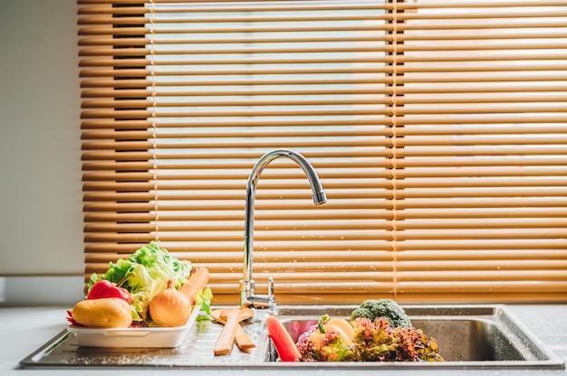 Lavado de verduras frescas en el fregadero con grifo