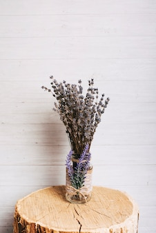 La lavanda florece en la botella de cristal sobre el tocón de madera del árbol contra fondo de madera