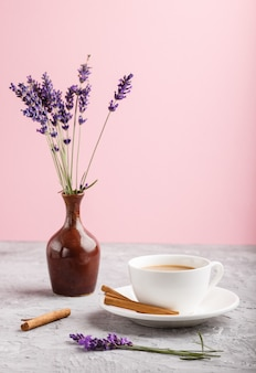 Lavanda púrpura en jarra de cerámica y una taza de café sobre un fondo gris y rosa