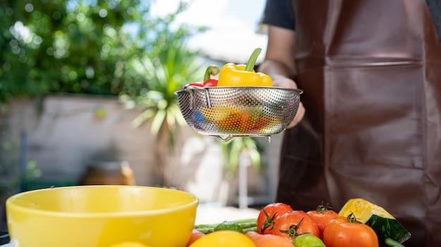 Él está lavando frutas y verduras.