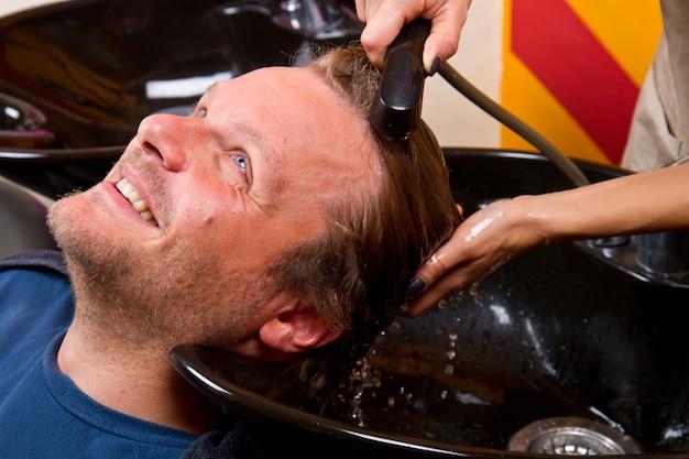 Lavar el cabello del hombre en el salón de belleza, peluquería.