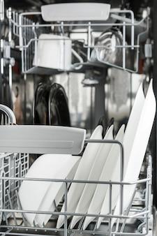 Lavar los platos en el lavaplatos.