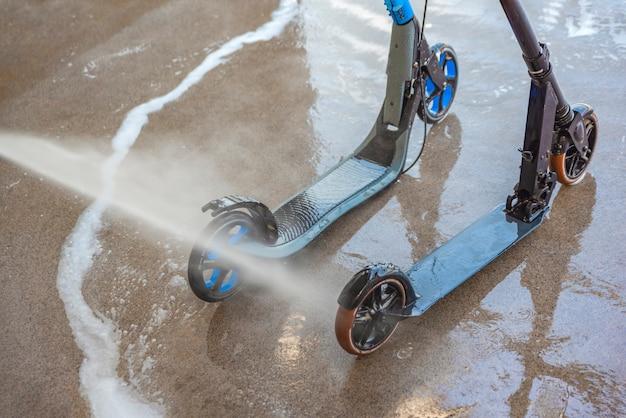 Lavar un scooter sucio en un túnel de lavado con agua a alta presión cuidado y limpieza del scooter