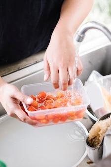 Lavar el tomate en el fregadero