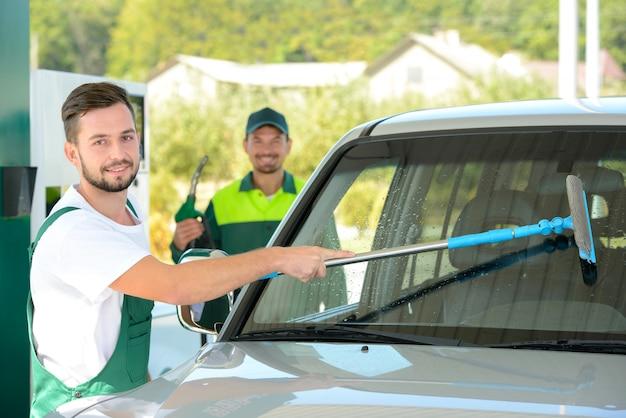 Lavar la ventanilla del auto mientras se llenan los autos de gasolina en la gasolinera