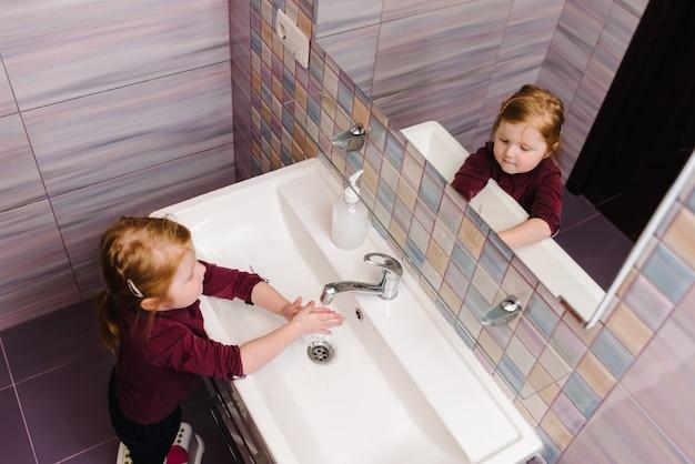 Lavarse las manos e higiene. niño, niño, lávese las manos con jabón antibacteriano, agua tibia frotándose las uñas y los dedos en el fregadero.