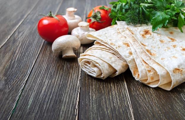 Lavash armenio y turco pan plano con tomates y champiñones en la mesa de madera
