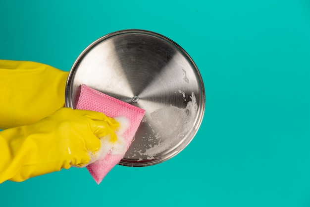 Lavavajillas con guantes amarillos sobre un azul.