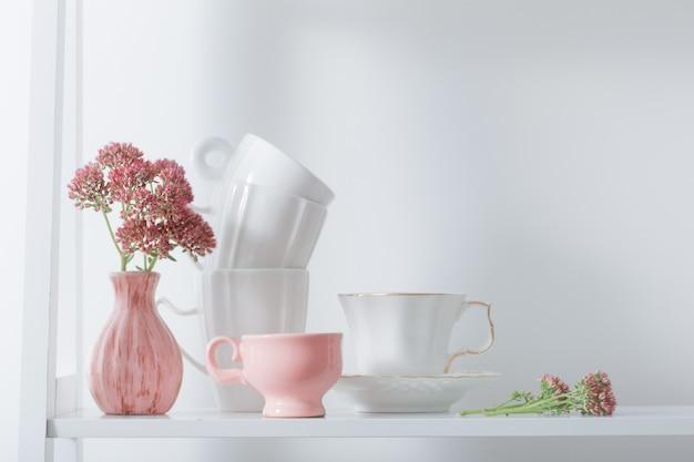 Lave los platos y las flores en un estante de madera.