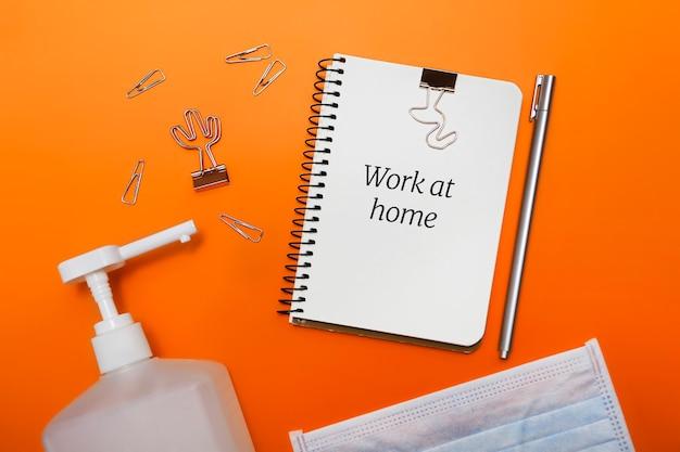 Lay flat con antiséptico, cuaderno en blanco y otra cancillería. quédese en casa y concepto de teletrabajo.