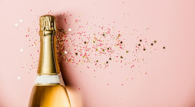 Lay flat de celebración. botella de champagne con chispas sobre fondo rosa.