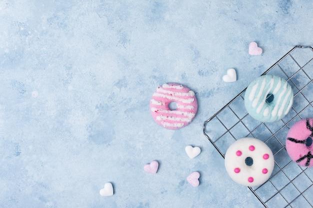 Lay flat de coloridas donas glaseadas con corazones y espacio de copia
