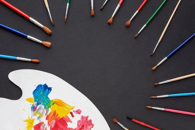 Lay flat de coloridos aquarelle y pinceles con espacio de copia