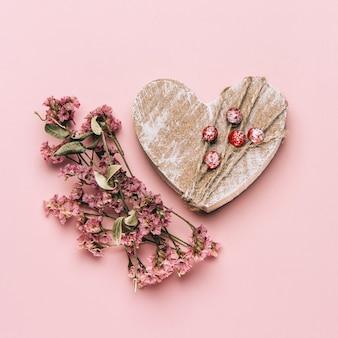 Lay flat creativo de corazón de madera sobre fondo de color suave con plantas naturales.