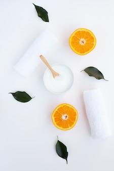 Lay flat de crema y rodajas de naranja sobre fondo blanco.