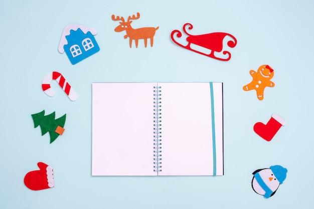 Lay flat con un cuaderno abierto vacío y juguetes navideños dispuestos alrededor del cuaderno sobre una superficie azul, copie el espacio.